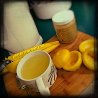 Picture showing a coffee mug filled with hot lemon and honey, with squeezed lemon peels, a kettle, and a pot of local honey sitting beside it.